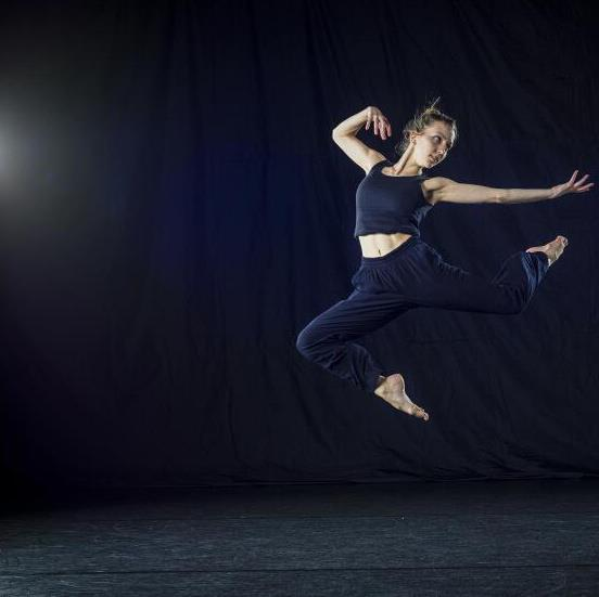 On a completely black stage, to the right of the image frame a dancer is leaping into the air, lifting both of her knees with neither foot touching the ground, as she extends her right arm and elongates her fingers towards the right. She is suspended in this motion as though flying or levitating upon a black background, while her black singlet and pants dissolve into the stage.