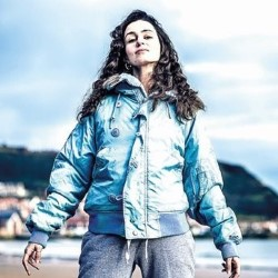 A small Italian woman with dark brown hair stands defiantly on a beach. She is wearing a light blue jacket and has her arms spread out to her sides. the camera looks up at her and she looks powerful.