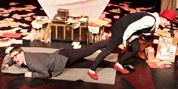 Two actors on stage, one dragging the other across the floor with various paraphernalia scattered across the floor.