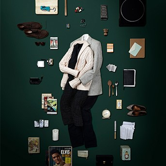 On a green background, a series of items including a pair of shoes, a record player, a notebook, some spoons, books, playing cards, sunglasses and keys lay around two sets of outfits that are styled as if being worn by two people lying together.