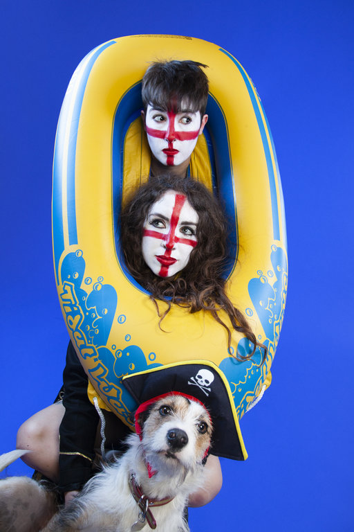 Sh!t Theatre Becca and Louise with their heads inside an inflatable boat with their face painted with the colours of the English flag while their dog sits in front with a pirate hat on.