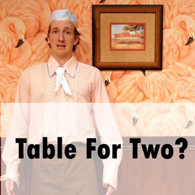 A mid-range photograph of a young man standing with a stupefied looking expression. He is wearing a soft peach-coloured dress shirt, with a white neck scarf, a white chef beanie, and a brown apron. With arms ready for action, he stands pressed against a half wood panelled wall, with the upper half of the wall covered in extravagant pink flamingo wallpaper. Hanging on the wall to the left of the man is a kitsch painting of a lamb standing on a sofa. At the base of the image is written 'Table For Two?'.
