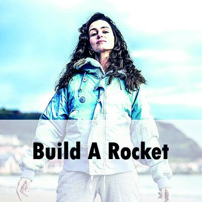 A small Italian woman with dark brown hair stands defiantly on a beach. She is wearing a light blue jacket and has her arms spread out to her sides. the camera looks up at her and she looks powerful. Across the bottom is written 'Build a Rocket'.