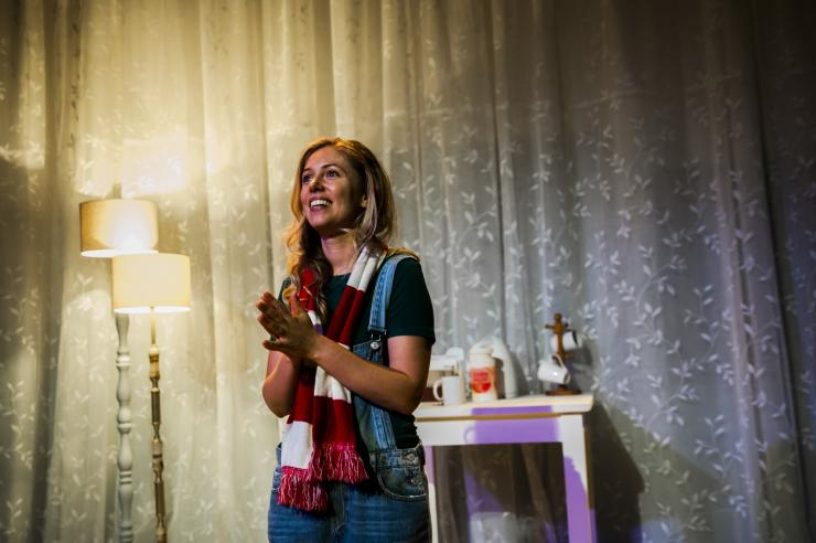 A blonde woman wearing a green shirt, blue denim overalls, and a red and white scarf stands in a living room. Behind her are white lace curtains, two tall lamps with warm lights, and a table with a kettle, a record player, and a set of keys.