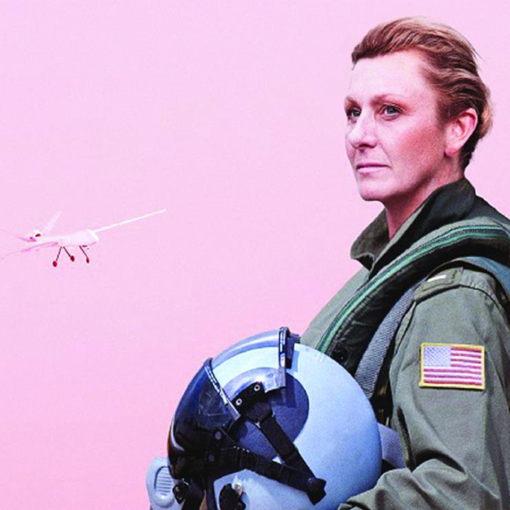 Actress in flight suit in front of pink background with white drone flying in the background.