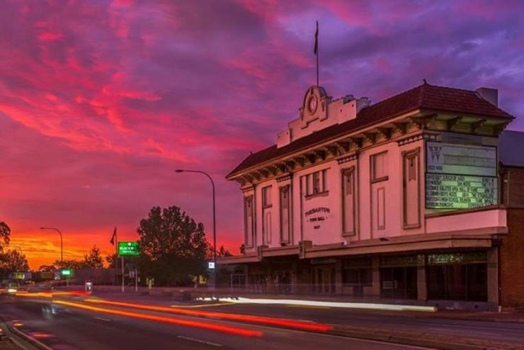 A photograph of the Thebarton Theatre facade at sunset: the neo colonial building is bathed in a soft pink light, as the brilliant colours of the setting sun to the west are exaggerated. Long strips of coloured light zoom along Henley Beach road in front of the theatre, achieved through a long exposure camera technique.