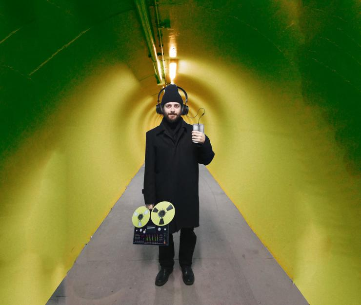 A man standing in a tunnel dressed in black with headphones and an old recording device.