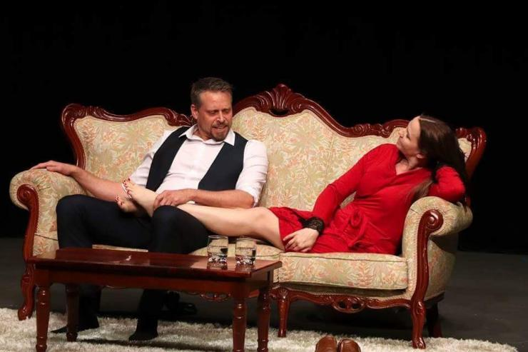 A couple are sitting on a Queen Ann style sofa in a luxurious living room setting. Both have removed their shoes, and the woman has her legs relaxing on the man's lap with her head reclined, she is looking towards the man as he speaks, holding her foot. She is wearing a short, long sleeved red wrap-around dress, and he is wearing a three piece suit but has removed his tie and jacket and has rolled up his sleeves. There are two tumblers on the small mahogany table in front of the couple.