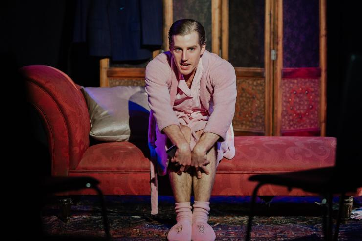 In this production picture, a young man, George, is the focal point in a matching pink pyjama set including lush gown, socks and slippers embroidered with golden 'G's'. He is sitting on a red Victorian-style setee, with an elaborate Persian rug underfoot, and a detailed oriental patrician behind him. He sits with his hands flamboyantly stretched over his knees; he is facing the viewer with piercing blue eyes and appears to be mid-sentence, perhaps revealing personal thoughts.