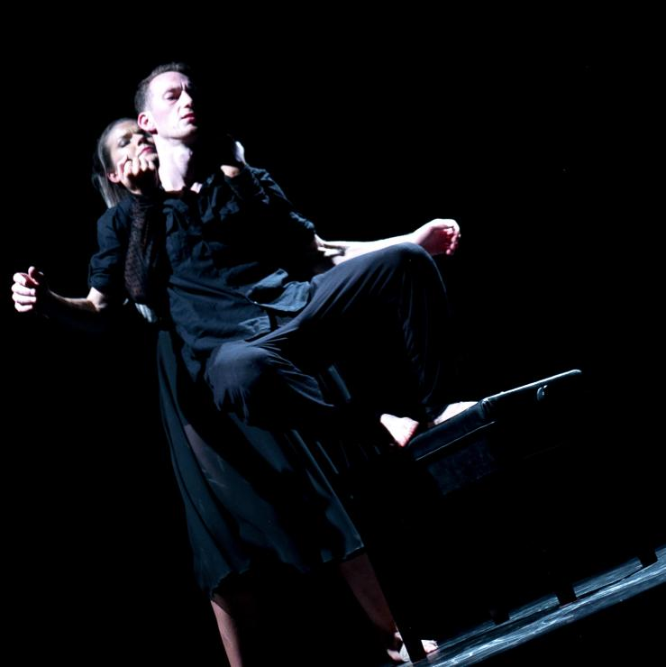 Two actors dressed in black dancing on stage.