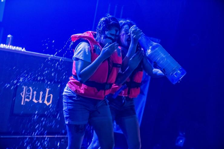 Sh!t Theatre Becca and Louise drinking from a large bottle on stage while wearing life vests.