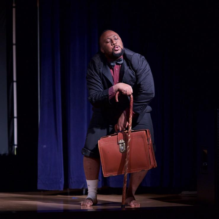 An actor on stage in a suit with rolled up pants, a suitcase and a cane.