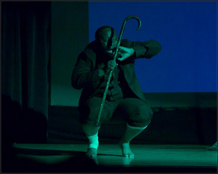 An actor squats on stage with rolled up suit pants and a cane.
