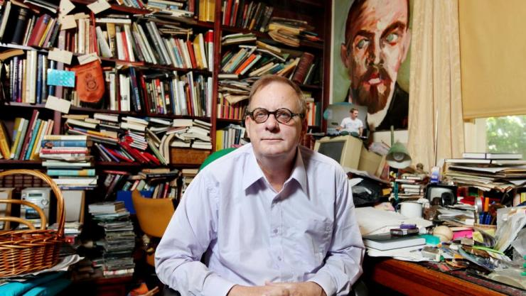 A man in his late-fifties is sitting at a desk at home. Behind him are bookshelves that cover the wall. They are full of books, all different shapes and colours. The man, Peter Goers, smiles directly at the camera.