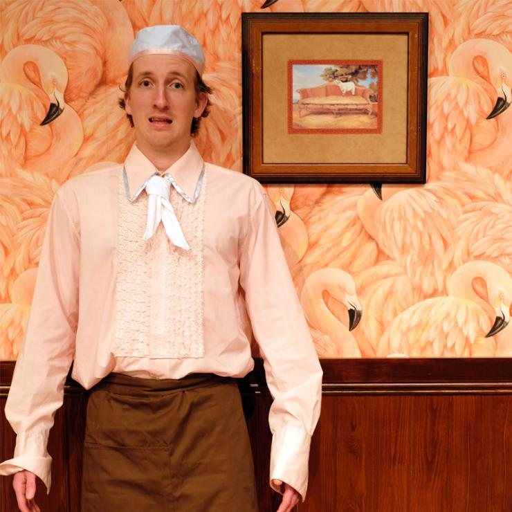 A mid-range photograph of a young man standing with a stupefied looking expression. He is wearing a soft peach-coloured dress shirt, with a white neck scarf, a white chef beanie, and a brown apron. With arms ready for action, he stands pressed against a half wood panelled wall, with the upper half of the wall covered in extravagant pink flamingo wallpaper. Hanging on the wall to the left of the man is a kitsch painting of a lamb standing on a sofa.