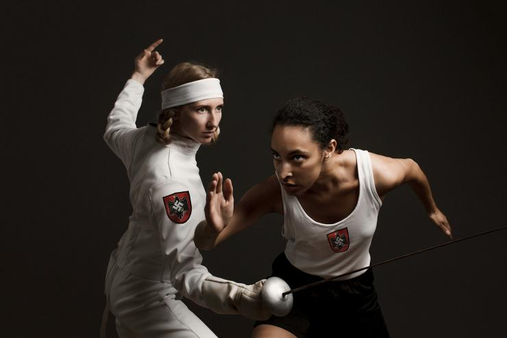 Two athletic women stand next to one another. The blonde haired women on the left is holding a fencing sword, and is positioned ready to spar in a match. She is wearing an all-white outfit with the red Nazi Germany insignia on the arm. The dark-haired woman on the right is positioned as if ready to run. She is also wearing an all-white outfit with the red Nazi Germany insignia on the arm. Both are facing into the middle of the image, looking off as if past the picture.