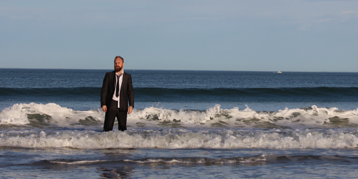 A man dressed in a suit standing in the ocean as small waves crash behind him.