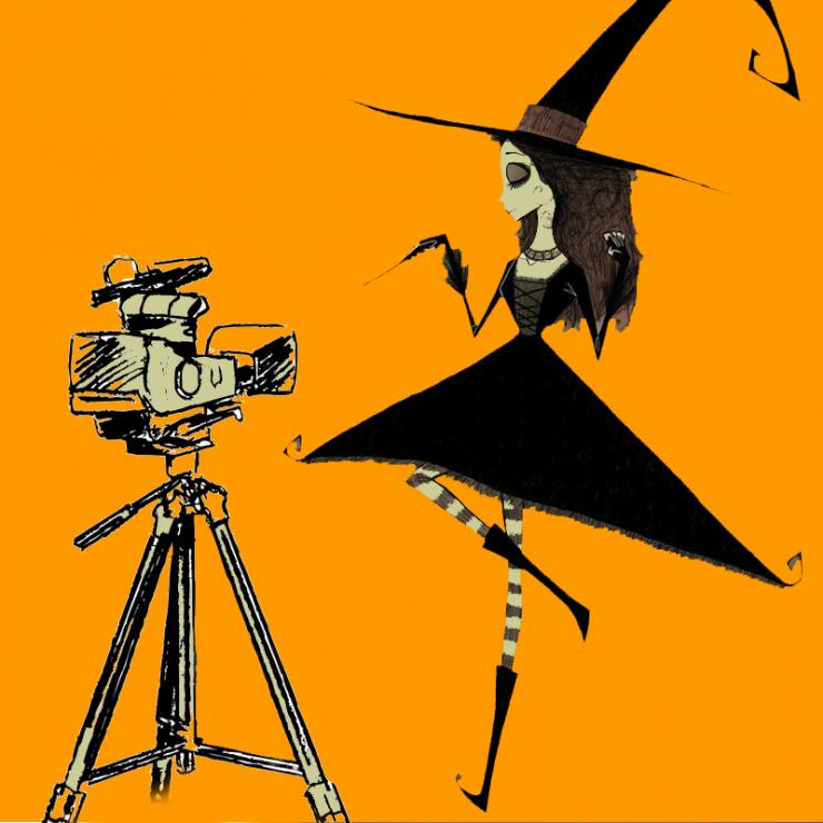 A cartoon image with two elements against a solid orange background. To the left is a large video camera on a tripod, drawn in a rough and scratchy style. On the right and facing the camera is a spindly young witch wearing an exaggeratedly large hat and dress with ornamental curly cues. She stands on one long, thin, stripe-stockinged leg, histrionically directing her wand at the camera.