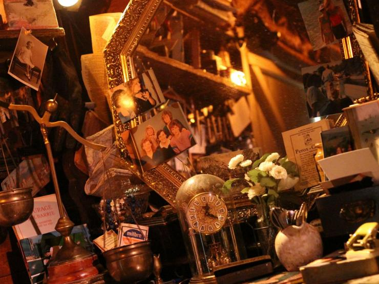 This is a production picture of an intricate set with a dull yellow light emanating a soft, warm glow across piles of ambiguous antique and personal items filling the close space. Distinguishable is a gilded framed mirror, an antique skeleton clock, brass scales, family photographs from across eras, books, maps, cards, vessels, a vase with white roses, and shelves with ambiguous bric-a-brac. In the blurred mirror reflection there are shelves stacked with unknown items next to a wooden door.