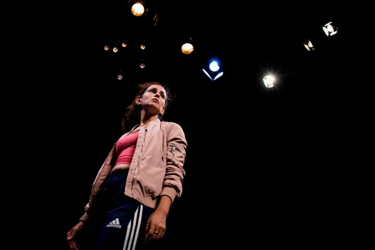A young dark-haired woman is looking off into the distance. She is wearing a light pink jacket, a dark pink top, and navy blue Adidas trackpants. The camera looks up at her and she looks powerful. Above her are a set of warm yellow lights, some large and some small.