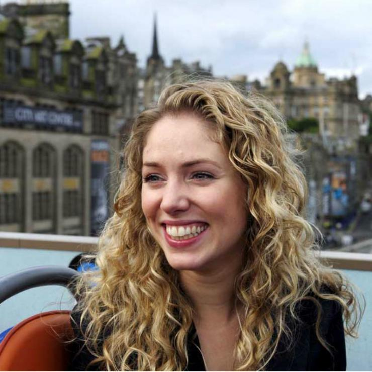 A photograph portrait of a young woman with a beaming smile and long wavy blonde hair, who is looking to the distance beyond the image frame. The top of her seat is visible, and behind her is an urban European landscape, with Victorian tenement buildings and a baroque steeple in the distance.