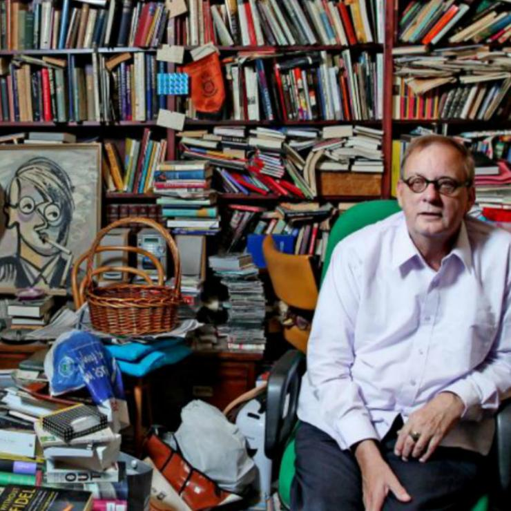 Peter Goers sits in a room full of books.