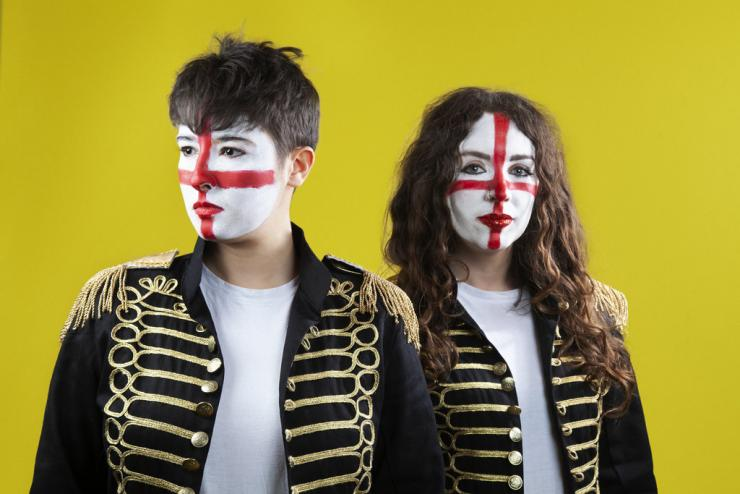 Sh!t Theatre Becca and Louise stand next to each other with their face painted with the colours of the English flag against a yellow background.
