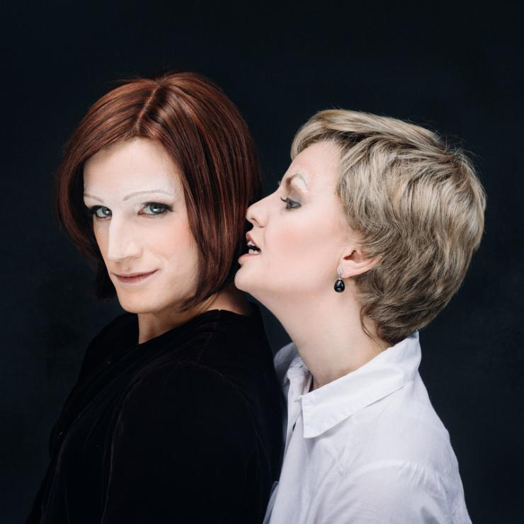 Two actors dressed as Julia Gillard and Julie Bishop embracing.
