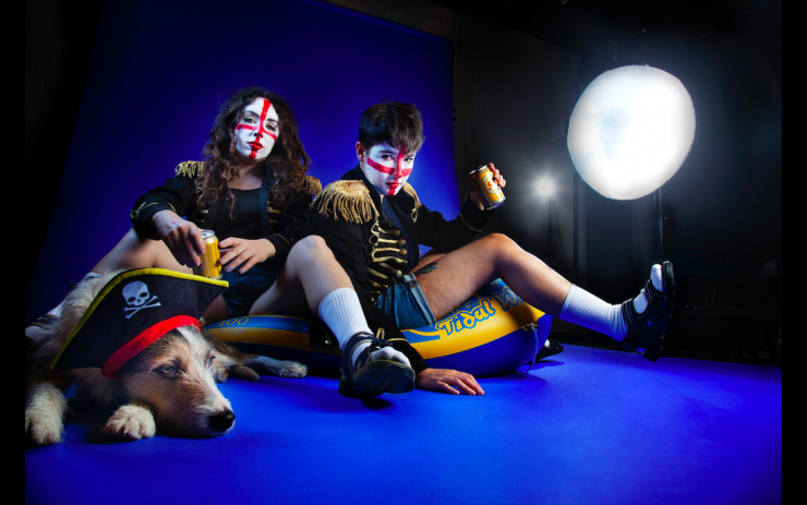 Sh!t Theatre Becca and Louise sit on an inflatable boat with their face painted with the colours of the English flag with beer in hand while their dog sits in front with a prate hat on.