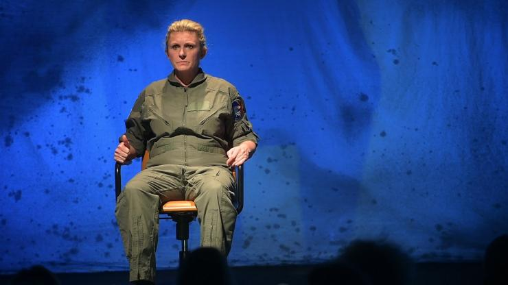 Actress sitting in chair on stage in flight suit.