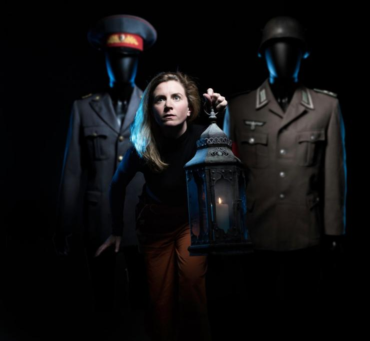 Actress stands in front of two uniformed mannequins while she leans forward with a lantern.